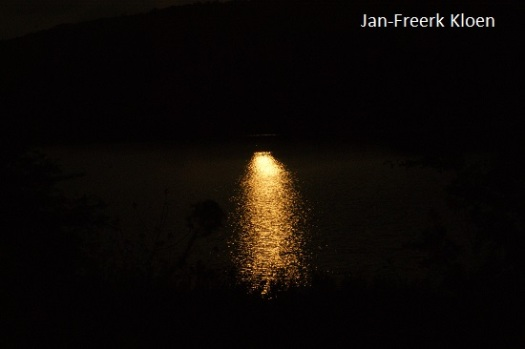 De zon, weerspiegeld op het water van de nevengeul