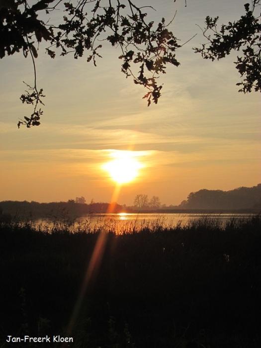 De zonsondergang boven de grote plas
