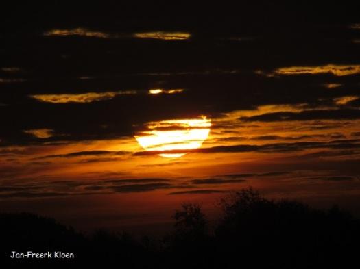 De laagstaande zon tussen de wolken